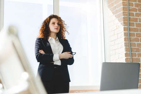 Portrait of a beautiful successful young business woman with red curly hair in the office interior stands near the window