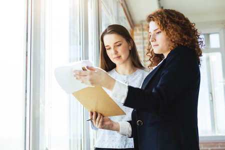 A beautiful young brunette woman and a red-haired woman are talking and discussing working moments near the window in the office Фото со стока