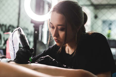 drawing of a tattoo on the leg close-up. Woman tattoo artist makes a drawing with a special machine in an art studio Фото со стока