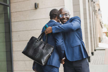Portrait of two black African American businessmen in suits shaking hands and hugging tightly outdoors. The joy of meeting good friends