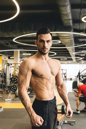Handsome young sporty male bodybuilder with naked torso posing in the gym