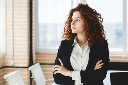 Portrait of a beautiful successful young business woman with red curly hair in an office interior stands with her arms crossed on her chest