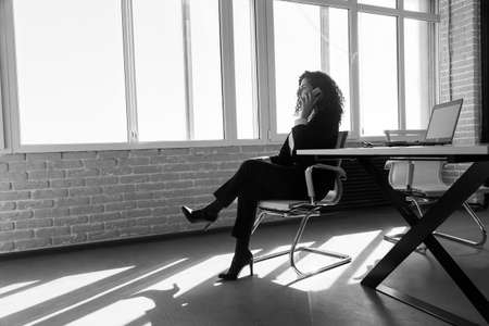 Portrait of a beautiful successful young business woman with red curly hair in an office interior sitting at a table and talking on the phone