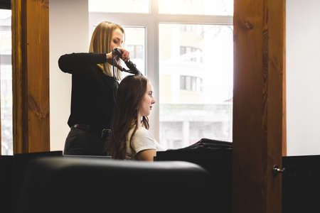 Master woman hairdresser gently curls hair curling girl in a beauty salon. Hair styling Фото со стока