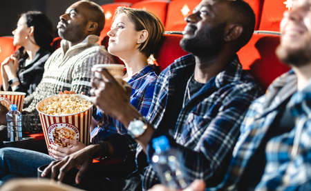 Friends watching a movie in the cinema with popcorn. People sit in the armchairs of the cinema and look at the screen