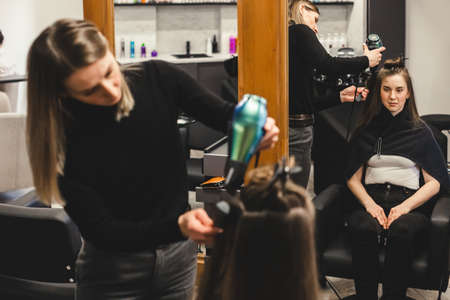 Master woman hairdresser dries the girls hair with a hairdryer after washing in a beauty salon.