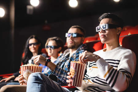 Friends are watching a movie in the cinema. People sit in the armchairs of the cinema and look at the screen with special glasses for 3D