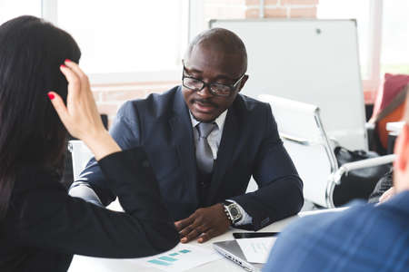 Mature afroamerican businessman to discuss information with a younger colleague. People working and communicating while sitting at the office desk together with colleagues sitting.