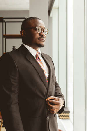 Portrait of a young successful businessman in a suit in the office. Close-up standing by the window