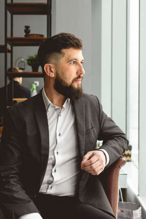 Portrait of a young successful businessman in a suit in the office. Close-up sitting in a chair by the window Фото со стока