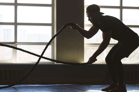Crossfit with ropes. The athlete is training in the gym. Silhouette photography Фото со стока