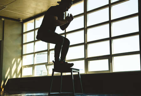 sports man jumps on a special platform in the gym opposite the window. Crossfit silhouette shot Фото со стока