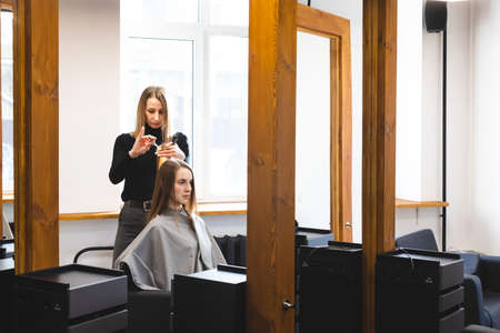 The master hairdresser cuts the ends of the hair after washing and in the beauty salon.