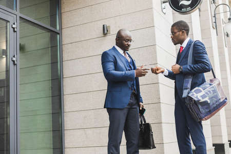 Portrait of two black African American businessman in suits exchanging business cards and contacts outdoors. Фото со стока