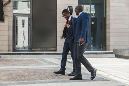 Two dark-skinned african american businessmen in suits and glasses walk outdoors in the city and discuss business