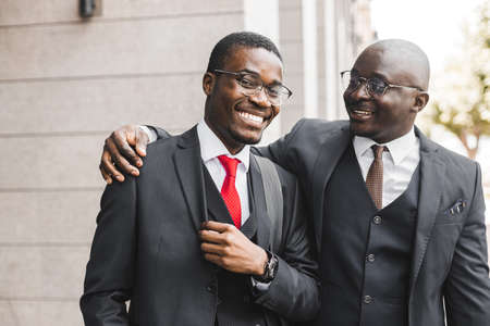Meeting of two long-time friends of black African American businessman in suits outdoors Фото со стока