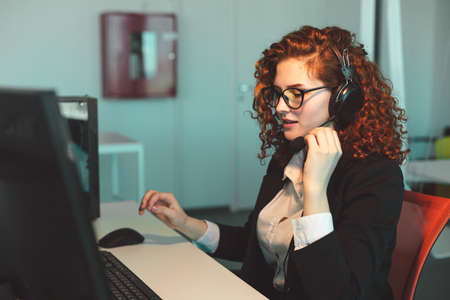 Portrait of a beautiful young woman operator with red curly hair and glasses in the interior of the call center office works at the computer and uses a special headset for calls