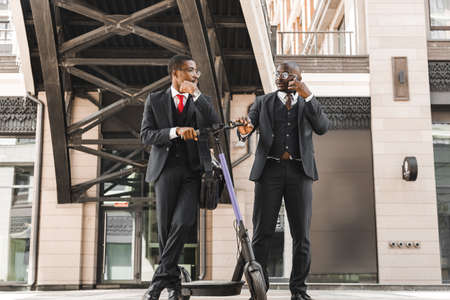 Meeting of two partners of black African American businessman in suits and glasses outdoors in a city block. Friendship and business partnership