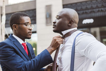Two black African American businessman friends before an important business meeting. One helps the other to put on a tie and straightens the suit