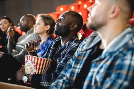 Friends are watching a movie in the cinema with popcorn. People sit in the armchairs of the cinema and look at the screen