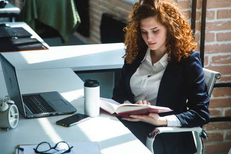 Portrait of a beautiful young business woman with red curly hair reading a book in the office. Successful career and leisure time and hobbies