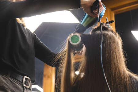 Master woman hairdresser dries the girls hair with a hairdryer and combs after washing in the beauty salon