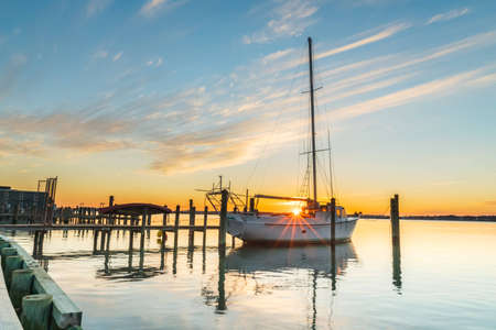 warmer: The sun sets as a sailboat rests at the dock waiting for warmer days and its next excursion.