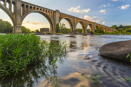 The graceful arches of a railroad bridge spanning the James River in Virginia are illuminated by the setting sun. 스톡 콘텐츠
