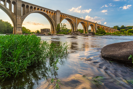 The graceful arches of a railroad bridge spanning the James River in Virginia are illuminated by the setting sun.