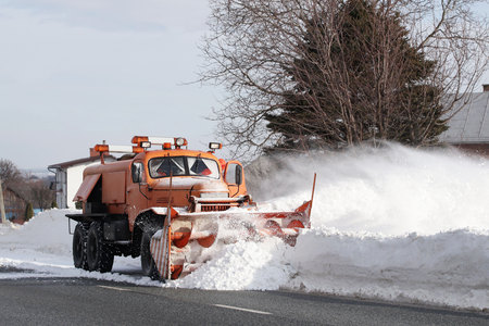 A large car with a plow clears the road from snow. Orange cargo special equipment is struggling with the elements in winter. Removing the effects of the snowstorm. Difficulties in traffic.Frozen water. Imagens