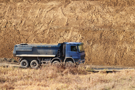 A heavy four-axle dump truck of blue drives along a dirt road against the background of a clay embankment. Career and road works. Drivers profession. Transportation of materials for the landscape