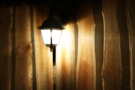 Glowing street lamp on the background of a wooden fence at night. Light permeates the darkness. Street lighting. Creating a cozy and romantic atmosphere. Elements of scenery and design. Stok Fotoğraf