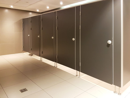 Doors in the public toilet. Interior in beige tones. Place of need for people. Restroom in public areas of urban infrastructure. Interior of public spaces. Wooden furniture and fittings.