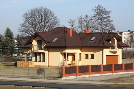 Jaslo, Poland - 2 16 2019: The project of a modern villa. Project of a small villa with yellow walls and a brown roof. Rear and front courtyard of a private territory enclosed by a fence.