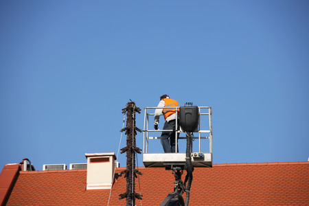 The worker in overalls works at height in a building mechanical lifting basket. Repair and construction work on the red tile roof. Renovation of architectural monuments in the historic part. Stock Photo - 118479376
