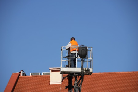The worker in overalls works at height in a building mechanical lifting basket. Repair and construction work on the red tile roof. Renovation of architectural monuments in the historic part. Stock Photo - 118479378