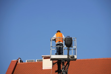 The worker in overalls works at height in a building mechanical lifting basket. Repair and construction work on the red tile roof. Renovation of architectural monuments in the historic part. 免版税图像