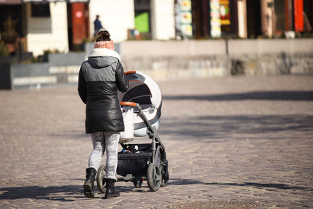 A young girl walks with a child s Kali in the historical center of a European city. Raising a child outdoors on a sunny, clear day. Clothes for a young mother. Family life in the city. Reklamní fotografie - 118479412