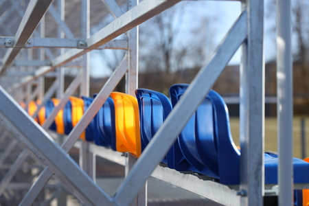 New stands on the football field of metal light construction with plastic seats in blue and yellow. Places for fans in the stadium. Going to the audience for sports competitions. Shelter from the run.