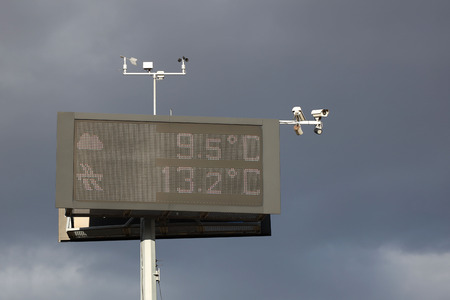 Electronic information board measuring temperature against the backdrop of thunderclouds. Security cameras and weather sensors. Infrastructure assistance to drivers on the highway. Warning of weather. Stock Photo