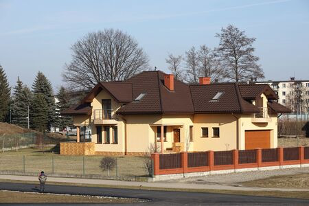 Jaslo, Poland - 2 16 2019: The project of a modern villa. Project of a small villa with yellow walls and a brown roof. Rear and front courtyard of a private territory enclosed by a fence. Editöryel