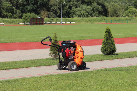 Orange mechanical device for cleaning and the formation of lawn sports objects in the open air against the background of a green football field, treadmill, bushes and trees. Technology work with green. Stockfoto