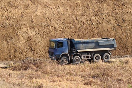 A heavy four-axle dump truck of blue drives along a dirt road against the background of a clay embankment. Career and road works. Driver's profession. Transportation of materials for the landscape.