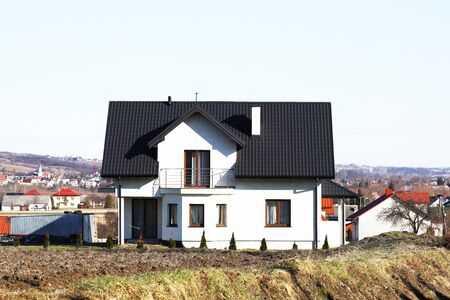 Jaslo, Poland - 9 2 2019: The project of a modern villa. Project of a small villa with clear walls and a brown roof. Rear and front courtyard of a private territory. Mastering new land and building.