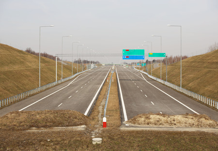 Unfinished two-lane highway with signposting signs. New road without cars. The development of transport infrastructure. Landscape design of the ring road of the metropolis.