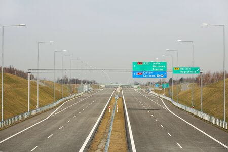 Rzeszow, Poland - 3 3 2019: Two-lane motorway with signposting signs. New road without cars. The development of transport infrastructure. Landscape design of the ring road of the metropolis.