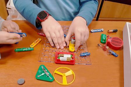 Los niños juegan a un constructor electromecánico. Edukatsiya generación en crecimiento. Circuitos electricos. Juguetes multicolores para el entrenamiento y desarrollo de niños y niñas. Física para principiantes. Foto de archivo