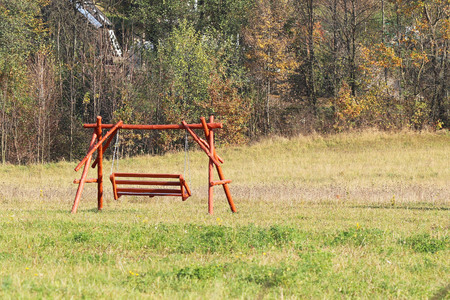 Plastic seat of a children's chain swing suspended above the earth. Adaptations for a playground. Memories of a joyful and carefree life. Use a metal chain. Activity of the growing up generation. Stockfoto
