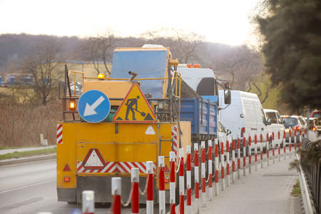 An orange street-cleaning machine stands in a traffic jam near the sidewalk designated by signal barriers. Road marking signs during road works. Restriction of traffic. Mechanized street cleaning Stock Photo