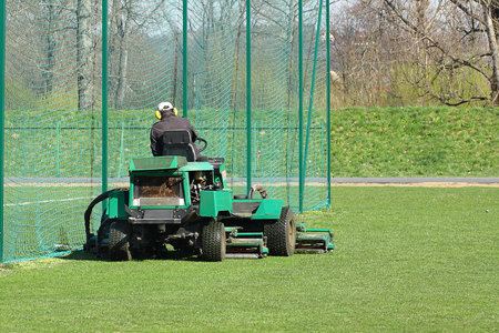 Worker on a large green lawn mower mows the grass on the football field. Landscape design and maintenance of green areas of the sports complex. Making grass stadium before the match. Human labor